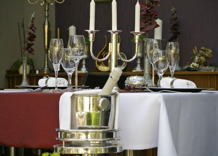 Megterített asztal a télikertben ezüst gyertyatartóval és dekorációval