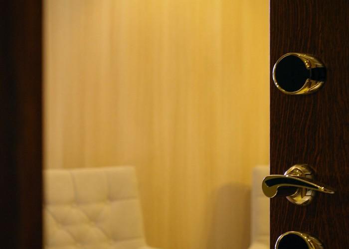 Családi lakosztály - érintőkártyás aranyozott bejárati ajtó, háttérben a bútorzat