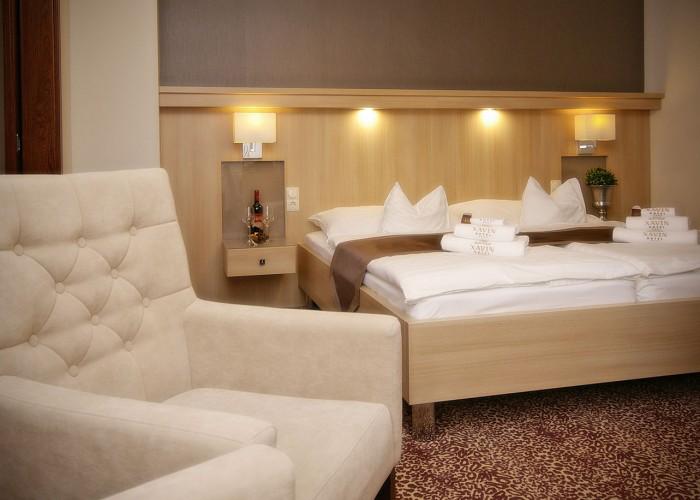 Családi lakosztály - ágy és székek, korszerű LED-es megvilágítás az ágy fejvégen