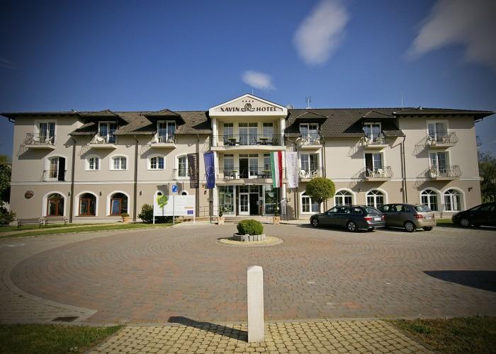 A szálloda főbejárata valamint homlokzata és a parkoló autók.