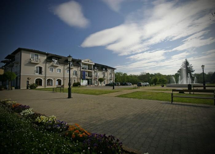 A Harkányi Xavin szállodájának utcaképe, háttérben a városi parkkal és szökőkúttal, valamint parkolóval.