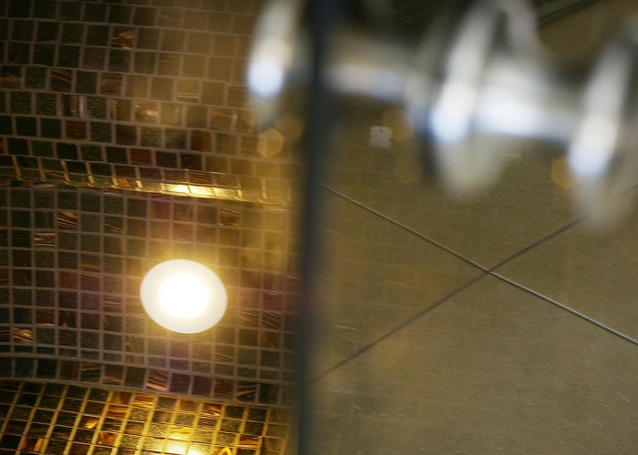 A gőzkabin ajtajának fogantyúja, háttérben a kabinban levő gőz és hangulatvilágítás, valamint a mozaikok.