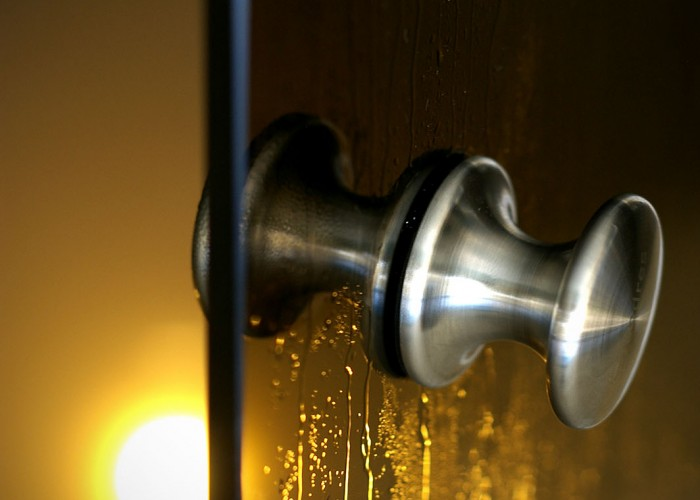 A harkányi Xavin Hotel gőzkabinjának ajtaja, háttérben a kabinban levő gőz és hangulatvilágítás.