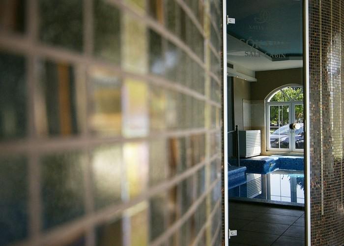 A szálloda sókabinjának ajtaja, háttérben a visszatükröződő merülő medence képe.