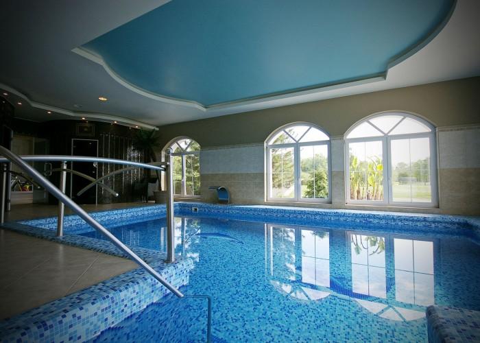 A harkányi Xavin Hotel merülő medencéje, háttérben a kilátással a szálloda mögötti parkra.