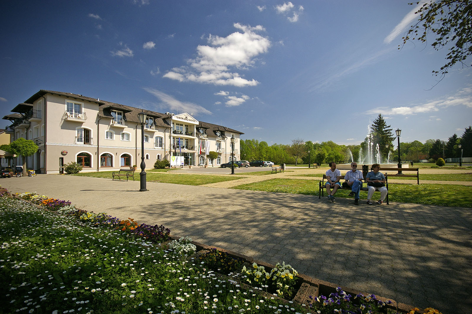 Szállodánk tavaszi hangulatban, háttérben a parkkal és a szökőkúttal illetve a parkolóval